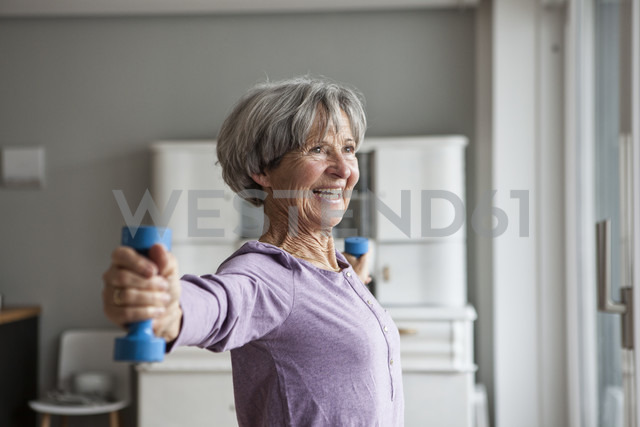 Portrait of happy senior woman doing fitness exercise with dumbbells at home - RBF004152 - Rainer Berg/Westend61