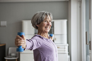 Portrait of happy senior woman doing fitness exercise with dumbbells at home - RBF004152