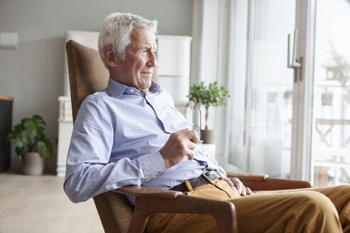 Portrait of senior man sitting on armchair at home looking through window - RBF004155