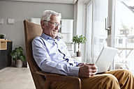 Portrait of senior man sitting on armchair at home using laptop - RBF004158