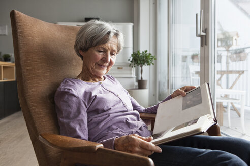 Portrait of senior woman sitting on armchair at home watching photo album - RBF004167