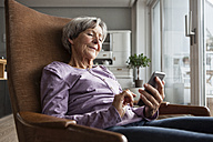 Portrait of senior woman sitting on armchair at home using smartphone - RBF004170