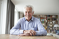 Portrait of confident senior man sitting at table in the living room - RBF004176