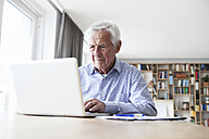 Portrait of senior man sitting at table using laptop - RBF004182