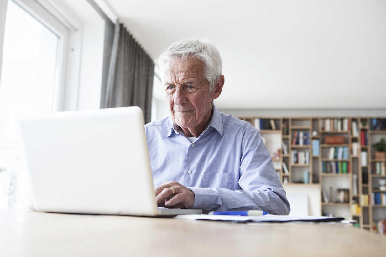 Portrait of senior man sitting at table using laptop - RBF004182 - Rainer Berg/Westend61