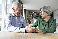 Happy senior couple holding hands at home - RBF004185