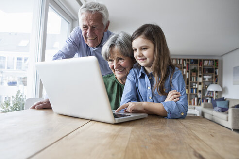 Grandparents and their granddaughter with laptop at home - RBF004188