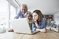 Grandparents and their granddaughter skyping with laptop at home - RBF004191