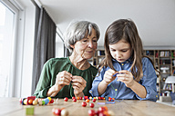 Grandmother and granddaughter stringing pearls - RBF004194