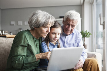 Grandparents and their granddaughter sitting together on the couch looking at digital tablet - RBF004206