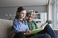 Grandmother and her granddaughter sitting together on the couch with a book - RBF004212