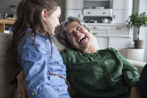 Laughing grandmother and her granddaughter on the couch at home - RBF004215