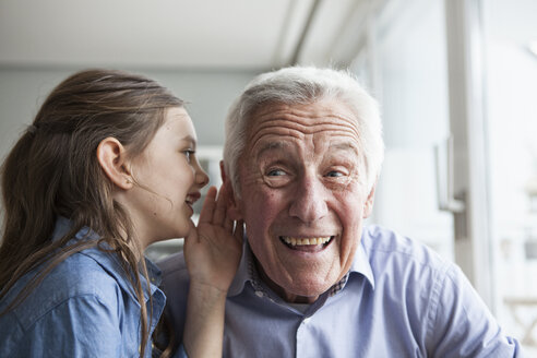 Granddaughter wispering something in the ear of her grandfather - RBF004218