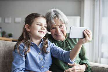 Grandmother and her granddaughter sitting together on the couch taking selfie with smartphone - RBF004221