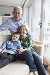 Family portrait of grandparents and their granddaughter at home - RBF004224