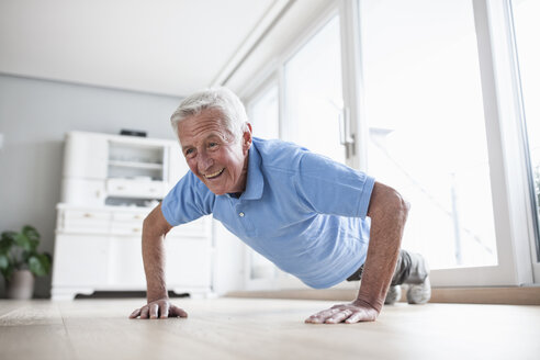 Portrait of senior man doing pushups at home - RBF004227