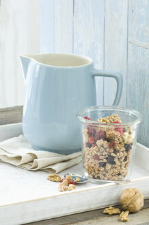 Glass of granola with walnuts, dried blueberries and raspberries and a milk jug - ASF005854