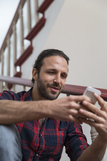 Man using cell phone in staircase - FKF001689