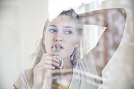 Portrait of young woman looking through windowpane while drinking water - FMKF002505