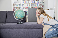 Yearning young woman crouching in her living room looking at globe globe - FMK002511