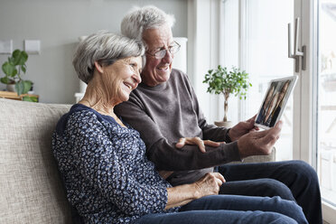 Senior couple sitting in their living room with digital tablet skyping with family - RBF004232