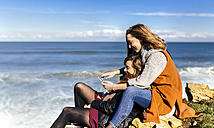Spain, Gijon, two young women having fun with a smartphone near the sea - MGOF001496