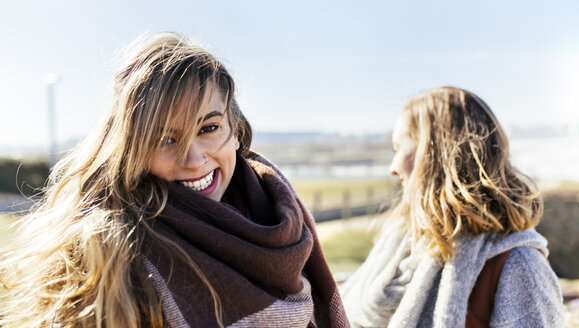 Portrait of happy young woman with friend outdoors - MGOF001499