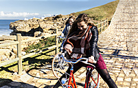 Two happy young women riding bicycle along a path - MGOF001502