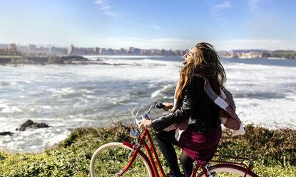 Spain, Gijon, playful young woman riding bicycle at the coast - MGOF001505