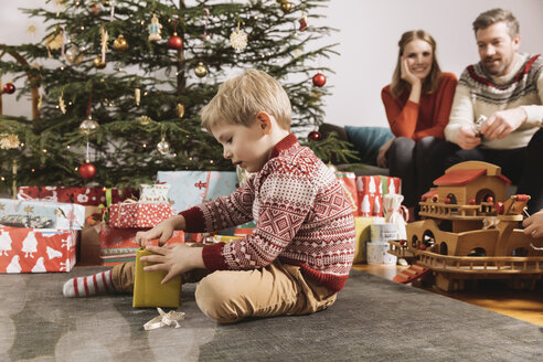 Little boy opening Christmas gift with parents watching in background - MFF002752