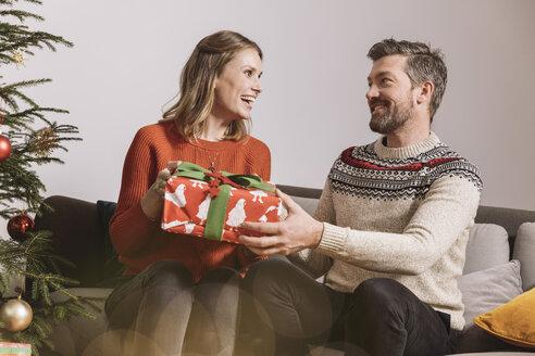 Couple exchanging a Christmas gift on sofa - MFF002755