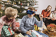 Brothers looking at new ski googles in front of Christmas tree - MFF002758