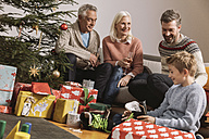 Three genarations family celebrating Christmas, children unwrapping presents - MFF002767