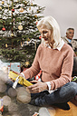 Senior woman looking at Christmas present in front of tree - MFF002770