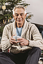Portrait of senior man with Christmas gift sitting in front of tree - MFF002773