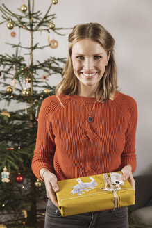 Portrait of woman with Christmas gift standing in front of tree - MFF002779
