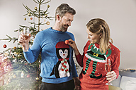 Two people with ugly Christmas sweaters laughing in front of tree - MFF002782