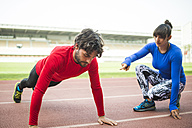 Athletes training for race in stadium - KIJF000213
