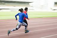 Athletes training for race in stadium - KIJF000222
