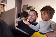 Father and his two little sons looking video on the laptop at home - VABF000287