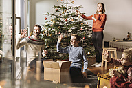 Family decorating Christmas tree, waving out of window - MFF002799