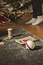 Christmas decoration lying on carpet, woman decorating tree in background - MFF002805