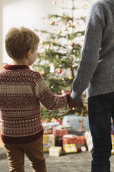 Two brothers waiting in front of Christmas tree looking at presents - MFF002808