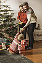 Parents giving Christmas gifts to little child - MFF002811