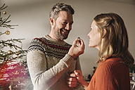 Man showing woman engagement ring by Christmas tree - MFF002820