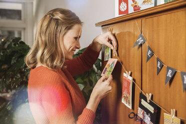 Woman hanging up Holiday cards for decoration - MFF002826