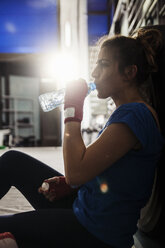 Female boxer taking a rest and drinking water - ZEDF000063