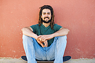 Portrait of smiling young man with dreadlocks and beard sitting on his skateboard in front of a reddish wall - KIJF000233