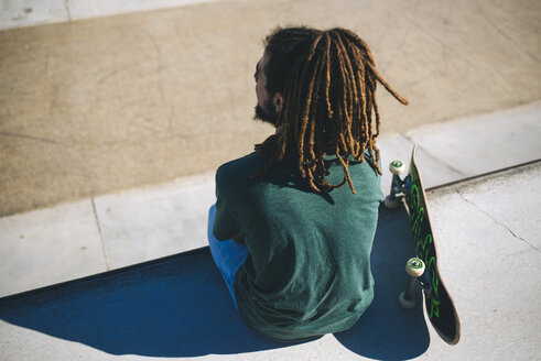 Back view of young man with dreadlocks sitting in a skatepark - KIJF000236