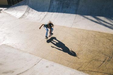 Young man with dreadlocks skateboarding in a skatepark - KIJF000239